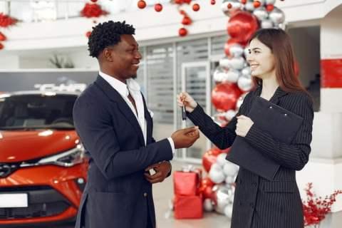 Woman Handing Keys to Man at Car Dealership