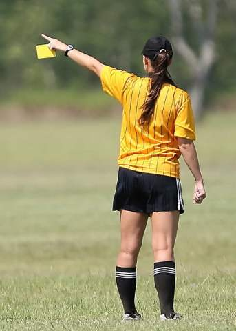 Female Soccer Referee Giving Yellow Card