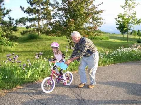 Grandfather Pushing Girl on Bicycle