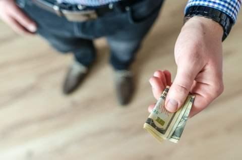 Handing Ten Dollar Bill