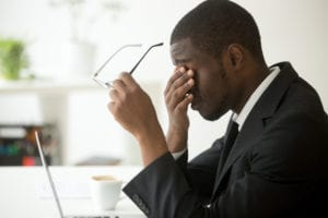 """Photograph of a man rubbing his eyes and holding his glasses in the other hand, from """"Health Benefits of Red Light Therapy: Legit or Hype?"""" from Green Smoothie Girl."""