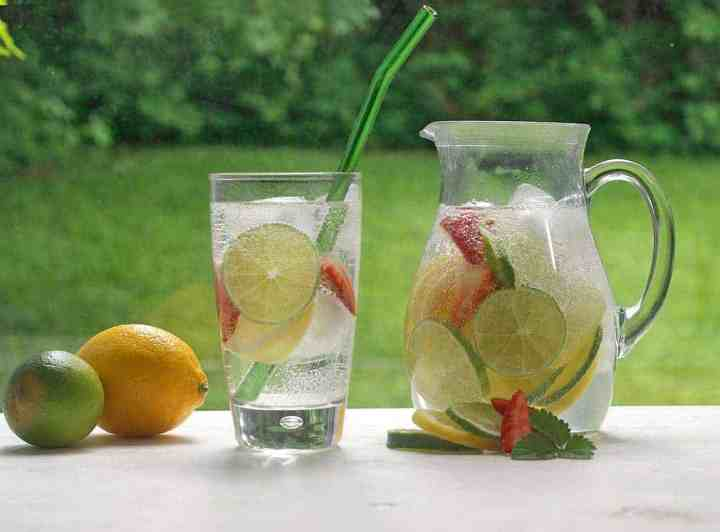 a pitcher and a glass full of infused water and limes and fruits with grass in the background.