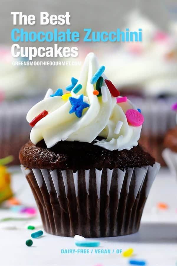 Chocolate cupcake with white icing with rainbow sprinkles on a white table.