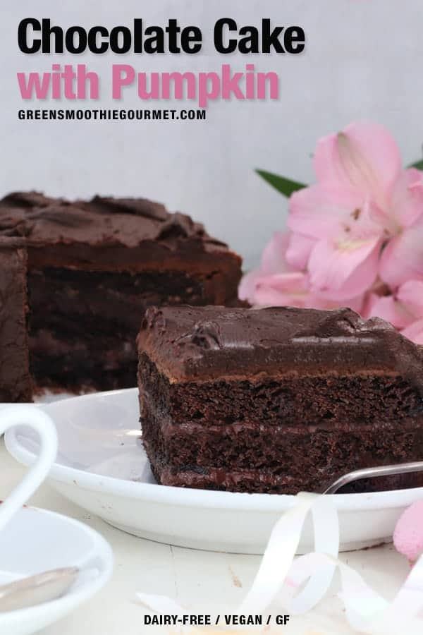 A slice of chocolate cake on a white dish with the whole cake behind it.
