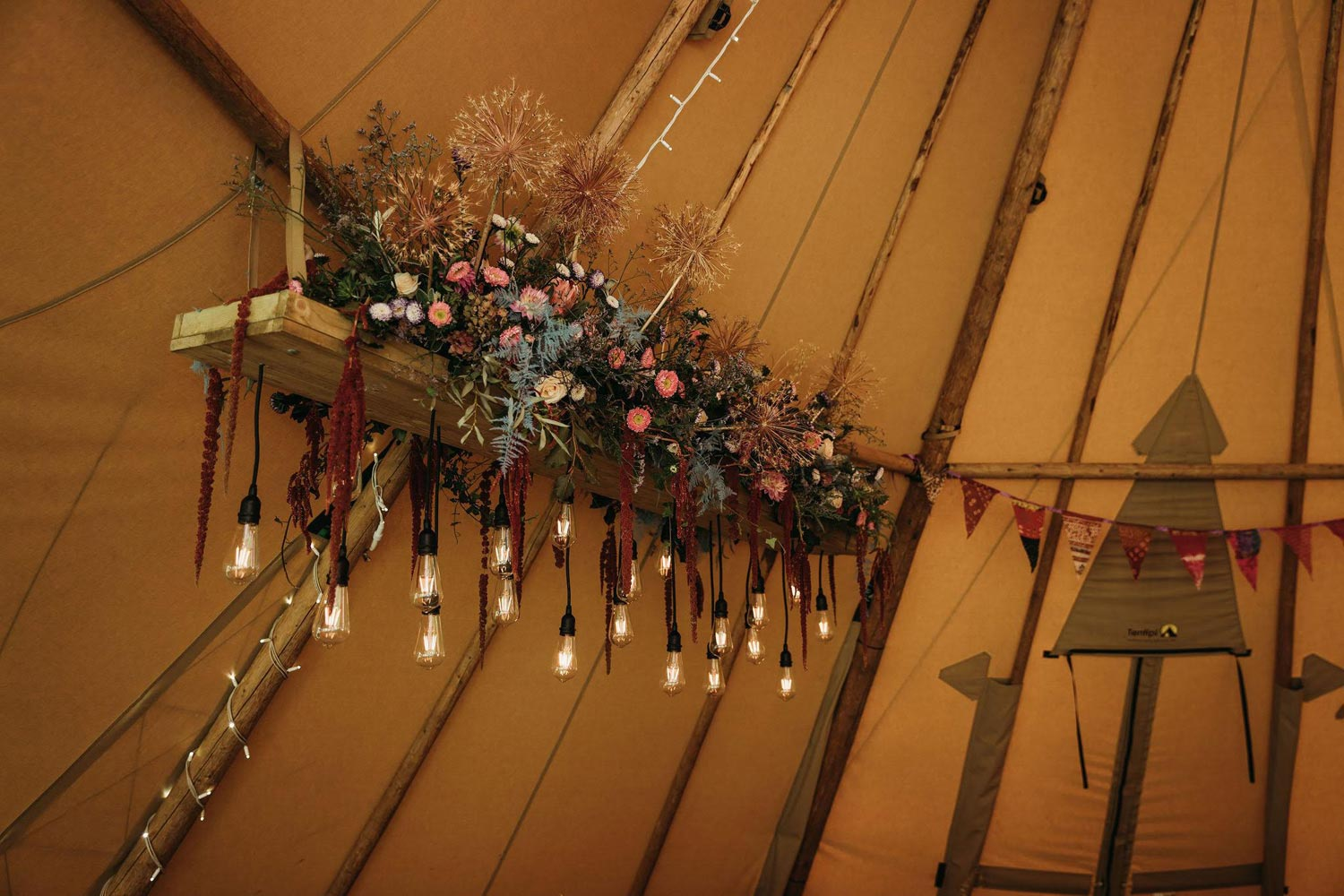 Hanging tipi floral decoration based around eco-friendly foraged foliage and seedheads