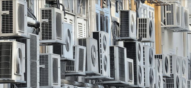 Many air conditioner units visible outside an apartment building in Singapore.