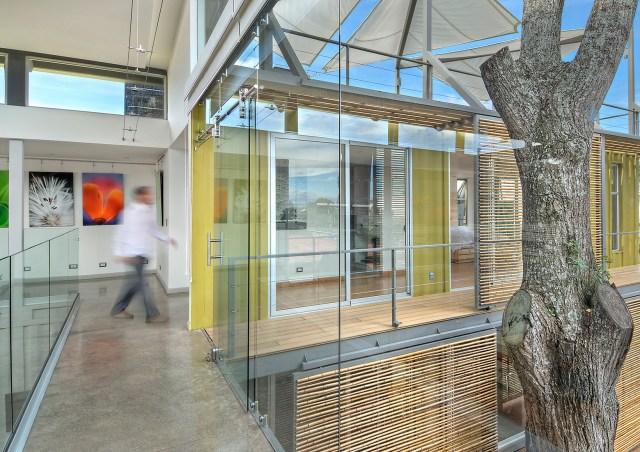 Corredor com generosas aberturas liga os quartos com a biblioteca. (Fonte: Homedit).