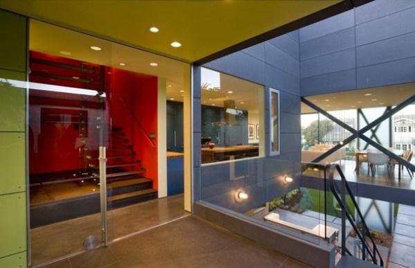 A porta de correr de vidro separa as áreas abertas com o interior da casa. Diferentes materiais foram utilizados como revestimento de paredes. (Fonte: Architect's List).