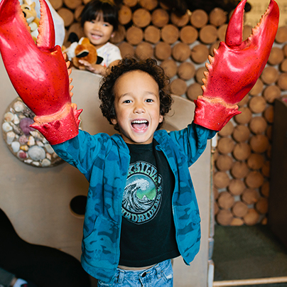 child with lobster hand at Children's Museum of Tacoma