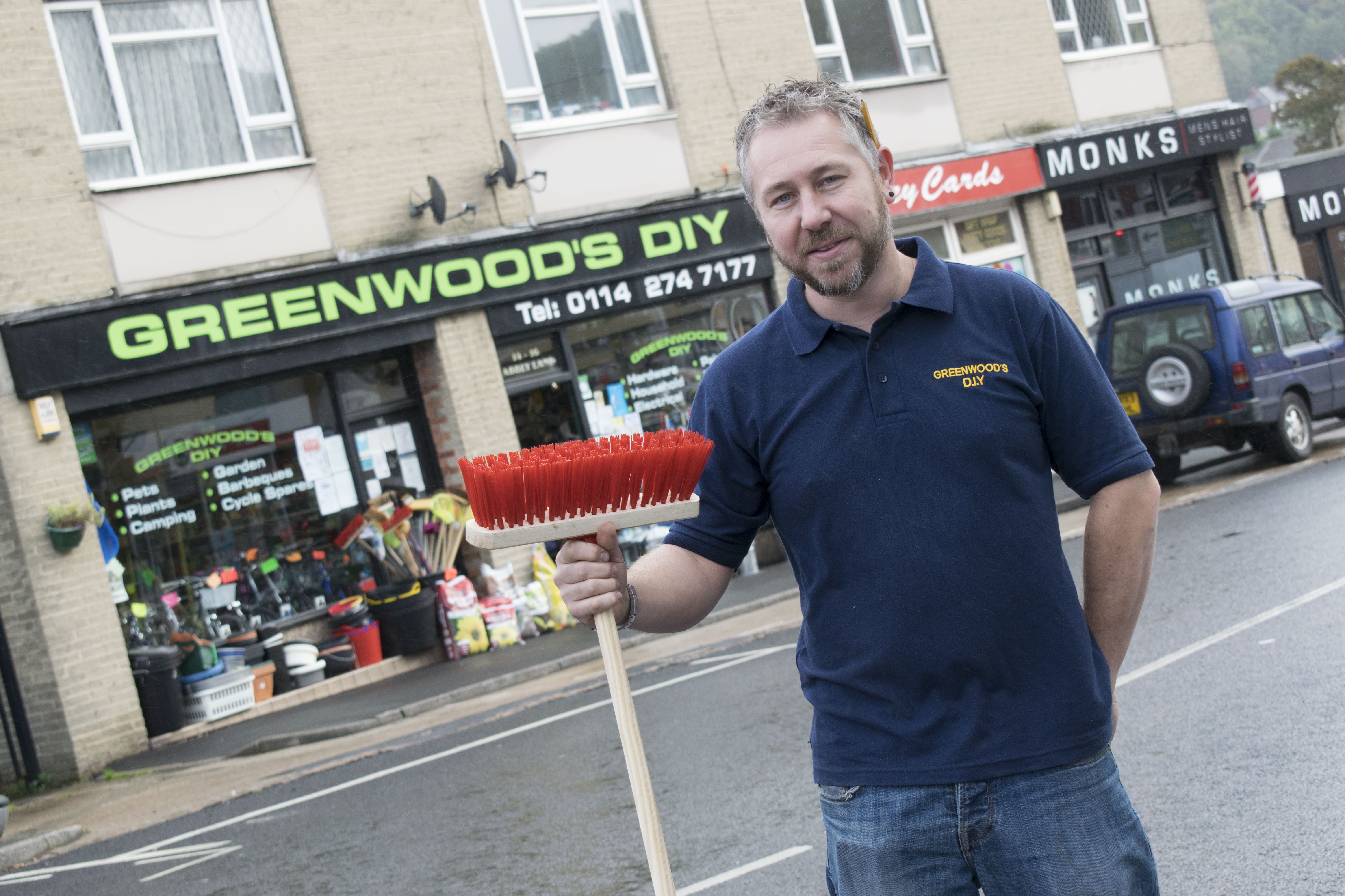 Nic outside the shop with a broom