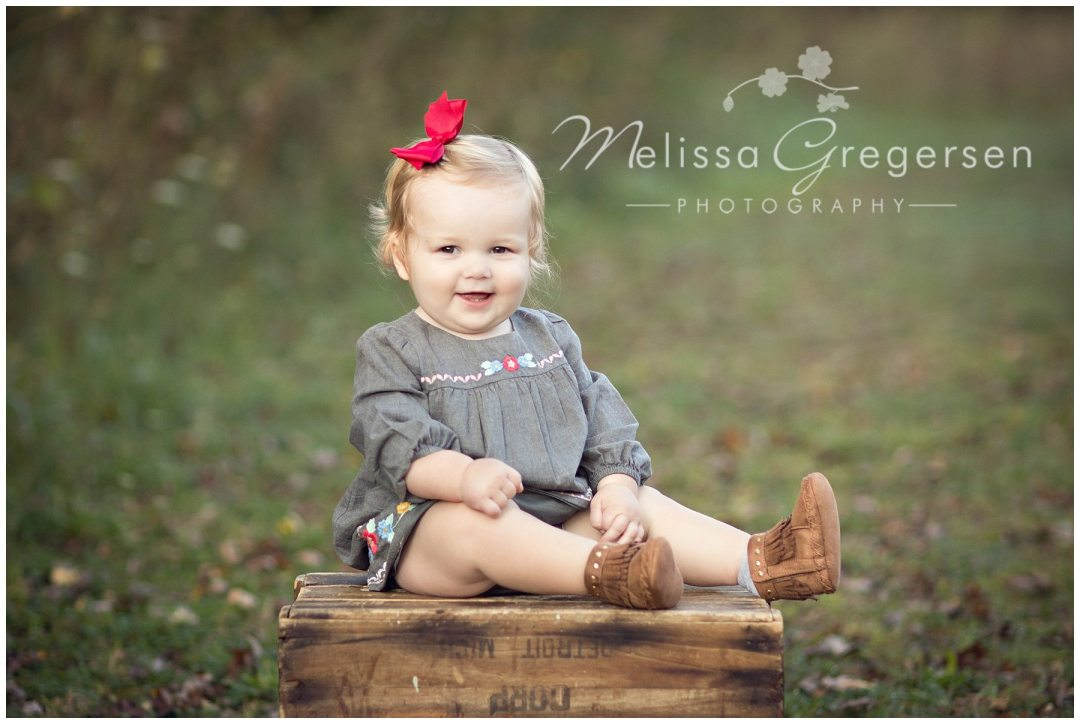 Adorable baby sitting on a brown box for photography session with family wearing a red bow