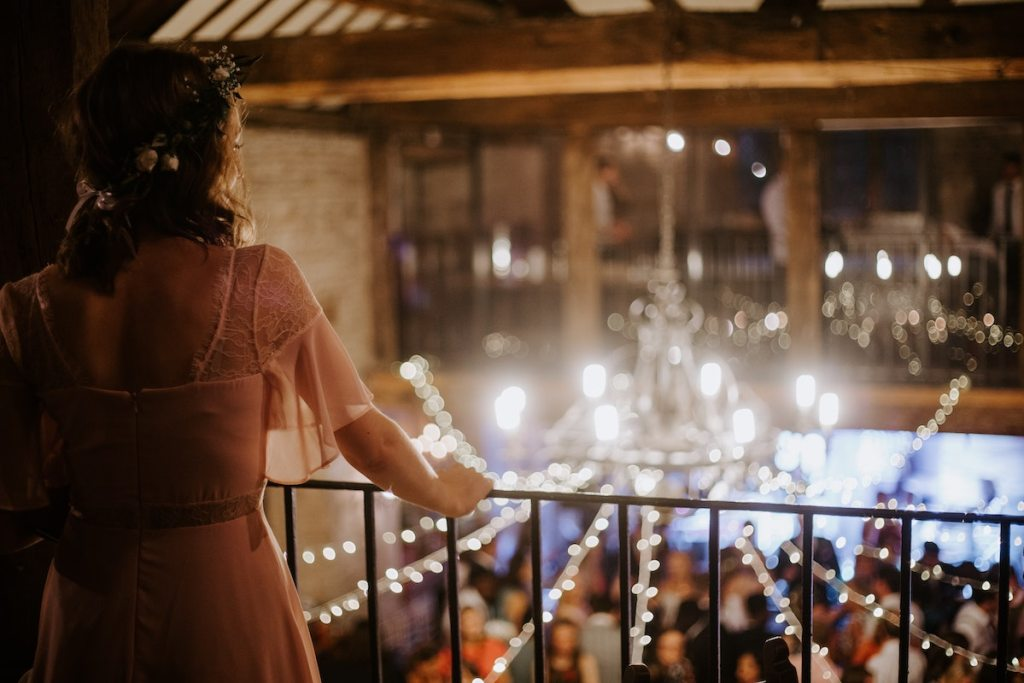 women standing on an indoor balcony overlooking a wedding below