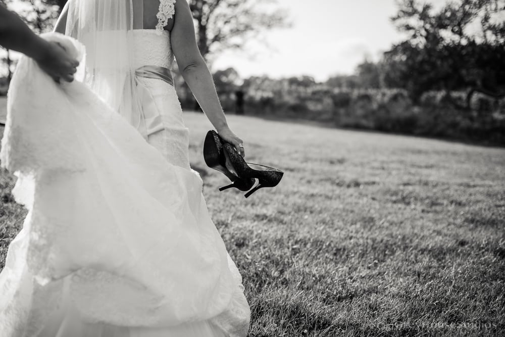 priam vineyards wedding photos bride walking with shoes