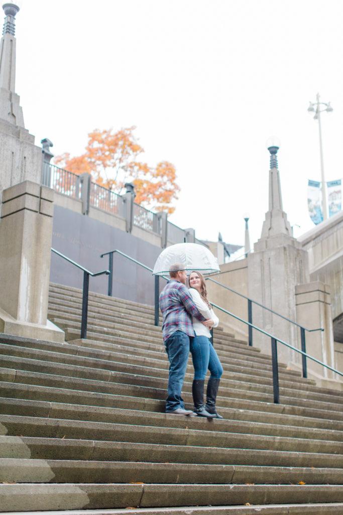 Couple posed with umbrella on stairs downtown Ottawa - Rainy Day Engagement Session Downtown Ottawa - Photo Locations   Grey Loft Studio - Ottawa Wedding Photographer & Videographer
