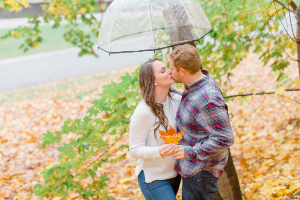 couple kissing holding a leaf with wedding date under umbrella - Rainy Day Engagement Session Downtown Ottawa - Photo Locations   Grey Loft Studio - Ottawa Wedding Photographer & Videographer