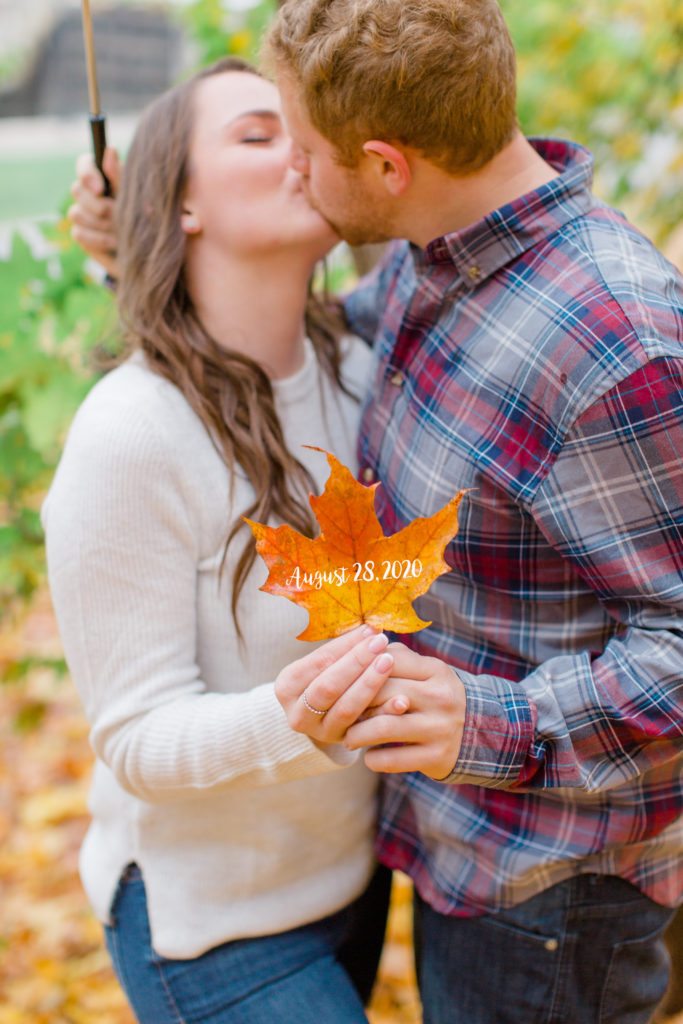 couple kissing in a fall engagement session with wedding date on leaf - Rainy Day Engagement Session Downtown Ottawa - Photo Locations   Grey Loft Studio - Ottawa Wedding Photographer & Videographer
