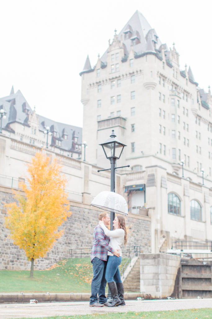 Couple standing in the rain during engagement session with the Locks and Chateau Laurier in the background  - Rainy Day Engagement Session Downtown Ottawa - Photo Locations   Grey Loft Studio - Ottawa Wedding Photographer & Videographer
