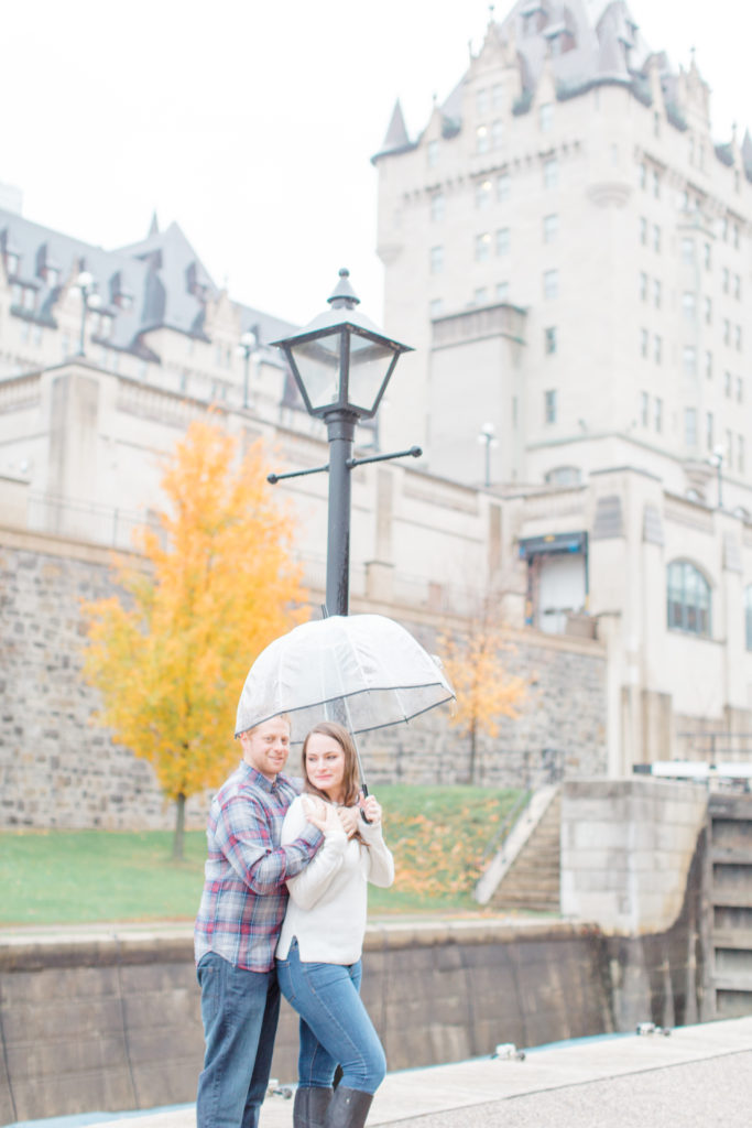 Couple standing in the rain during engagement session Chateau Laurier in the background