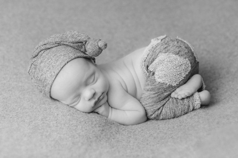 black and white newborn boy posed on a blanket with a hat