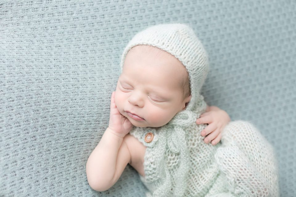 Baby with a light green knitted hat posed on a light green blanket