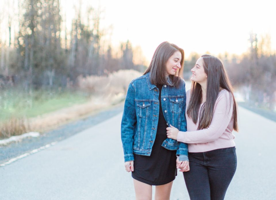 same sex lesbian engagement session during sunset, cute couple very much in love, jean jacket and pink sweater holding hands and walking on the road