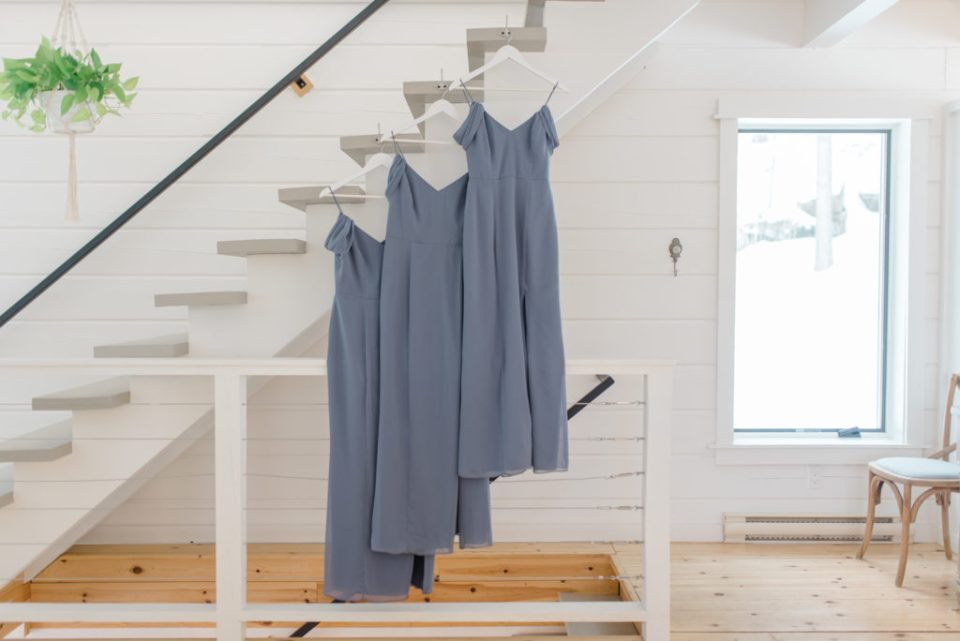 unique spot for hanging the bridesmaid dresses with white hangers - Matching white hangers - bridesmaids in blue robes - holding bouquets in water - sitting on a bed - quebec wedding photographer Wakefield bridgeottawa wedding photographer couple getting married in winter le belvedere wedding sunset grey loft studio couples in love affordable kanata photographer cheap wedding fun wedding romantic wedding bridesmaids