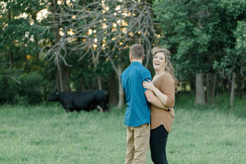 Cow Photobomb - Cows during Engagement Session - Poses during Engagement Session  Sunset - Natural Posing for Photo Session - Couples Photo Session Fun - Fun on the Farm - Farm Engagement Session - Blue and Brown Engagement Session Inspiration - Natural Engagement Session Posing - Ideas for what to wear for Engagement Photography, Modern Engagement Session Inspiration Wardrobe Ideas. Unsure of what to wear for your engagement photos, we've got you! Romantic brown with black leggings for Summer Engagement in Almonte. Grey Loft Studio is Ottawa's Wedding and Engagement Photographer for Real couples, showcasing photos that are modern, bright, and fun.