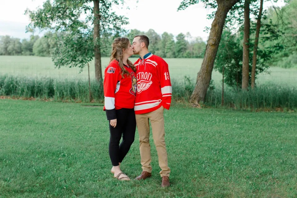 Ottawa Sens Jersey - Detroit Redwings Jersey - Engagement Session Inspiration. - Poses during Engagement Session  Sunset - Natural Posing for Photo Session - Couples Photo Session Fun - Fun on the Farm - Farm Engagement Session - Blue and Brown Engagement Session Inspiration - Natural Engagement Session Posing - Ideas for what to wear for Engagement Photography, Modern Engagement Session Inspiration Wardrobe Ideas. Unsure of what to wear for your engagement photos, we've got you! Romantic brown with black leggings for Summer Engagement in Almonte. Grey Loft Studio is Ottawa's Wedding and Engagement Photographer for Real couples, showcasing photos that are modern, bright, and fun.