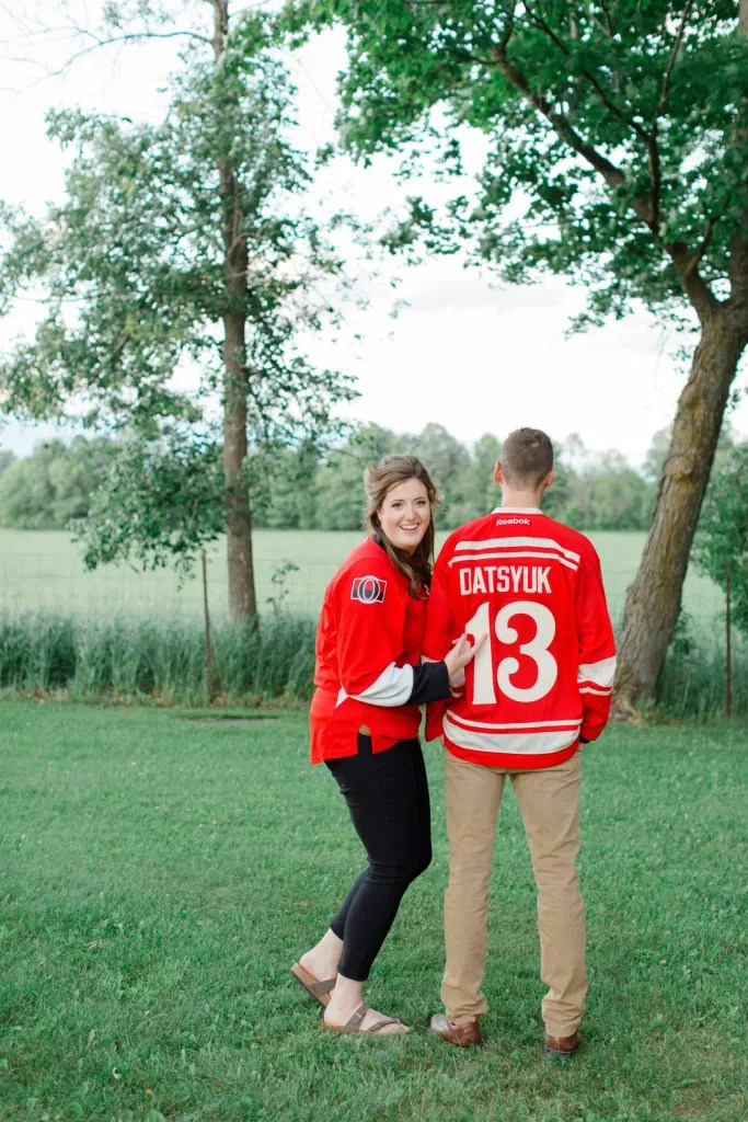 Ottawa Sens Jersey - Detroit Redwings Jersey - Datsyuk- Engagement Session Inspiration. - Poses during Engagement Session  Sunset - Natural Posing for Photo Session - Couples Photo Session Fun - Fun on the Farm - Farm Engagement Session - Blue and Brown Engagement Session Inspiration - Natural Engagement Session Posing - Ideas for what to wear for Engagement Photography, Modern Engagement Session Inspiration Wardrobe Ideas. Unsure of what to wear for your engagement photos, we've got you! Romantic brown with black leggings for Summer Engagement in Almonte. Grey Loft Studio is Ottawa's Wedding and Engagement Photographer for Real couples, showcasing photos that are modern, bright, and fun.