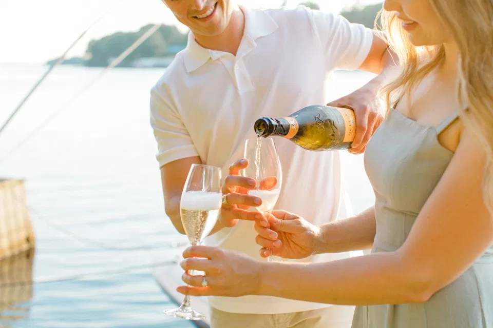 Pop the Champagne - Ideas for what to wear for Engagement Photography, Modern Engagement Session Inspiration Wardrobe Ideas. Unsure of what to wear for your engagement photos, we've got you! Romantic blue Romper and neutral Shirts and polo. Boat Shoes and Flip Flops. Engagement in Gananoque. Grey Loft Studio is Ottawa's Wedding and Engagement Photographer Videographer for Real couples, showcasing photos that are modern, bright, and fun.
