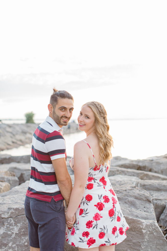 Cute Poses on the beach - Ideas for what to wear for Engagement Photography, Modern Engagement Session Inspiration Wardrobe Ideas. Unsure of what to wear for your engagement photos, we've got you! Romantic floral dress. Navy, Burgundy, & White T-shirt Polo & Navy shorts . Boat Shoes and Fancy. beaded sandals. Engagement at Britannia Beach, Nepean. Grey Loft Studio is Ottawa's Wedding and Engagement Photographer Videographer for Real couples, showcasing photos that are modern, bright, and fun.