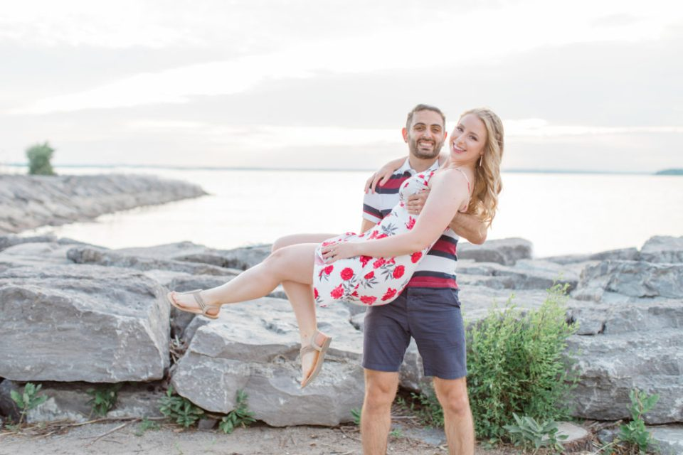 Cute Poses on the beach-  Lift and Twirl - Ideas for what to wear for Engagement Photography, Modern Engagement Session Inspiration Wardrobe Ideas. Unsure of what to wear for your engagement photos, we've got you! Romantic floral dress. Navy, Burgundy, & White T-shirt Polo & Navy shorts . Boat Shoes and Fancy. beaded sandals. Engagement at Britannia Beach, Nepean. Grey Loft Studio is Ottawa's Wedding and Engagement Photographer Videographer for Real couples, showcasing photos that are modern, bright, and fun.