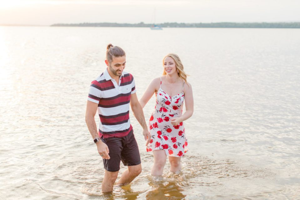 Cute Poses on the beach in Water - Ideas for what to wear for Engagement Photography, Modern Engagement Session Inspiration Wardrobe Ideas. Unsure of what to wear for your engagement photos, we've got you! Romantic floral dress. Navy, Burgundy, & White T-shirt Polo & Navy shorts . Boat Shoes and Fancy. beaded sandals. Engagement at Britannia Beach, Nepean. Grey Loft Studio is Ottawa's Wedding and Engagement Photographer Videographer for Real couples, showcasing photos that are modern, bright, and fun.