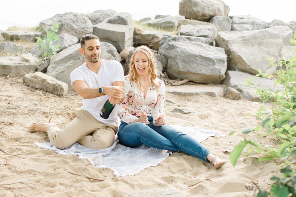 Popping the Champagne -Sitting on the Beach - Ideas for what to wear for Engagement Photography, Modern Engagement Session Inspiration Wardrobe Ideas. Unsure of what to wear for your engagement photos, we've got you! Romantic floral shirt & jeans.  White T-shirt & neutral pants . Boat Shoes and Fancy. beaded sandals. Engagement at Petrie Island, Orleans. Grey Loft Studio is Ottawa's Wedding and Engagement Photographer Videographer for Real couples, showcasing photos that are modern, bright, and fun.