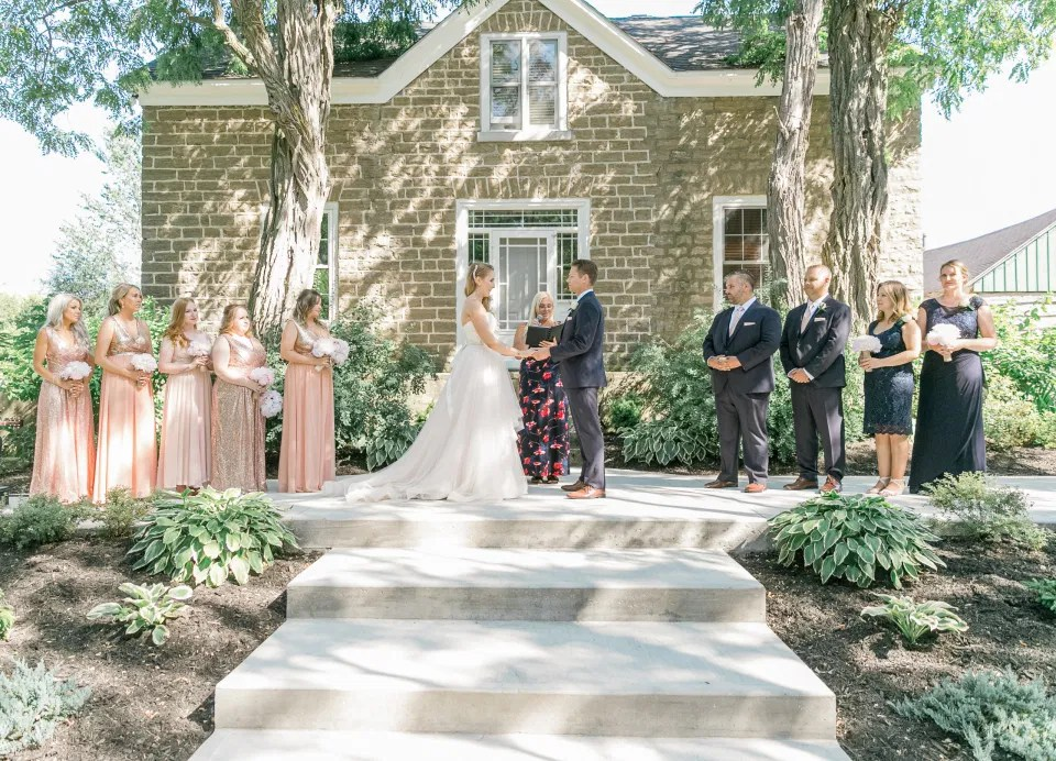 Bride and Groom Holding Hands During Wedding Ceremony -  Stonefields Estate-  Bright and Airy - Natural Wedding Posing - Modern Wedding Blush &. Navy Wardrobe inspiration-  Romantic white with greenery, blush and navy theme. Grey Loft Studio is Stonefields Wedding and Engagement Photographer for Real couples, showcasing photos that are modern, bright, and fun.