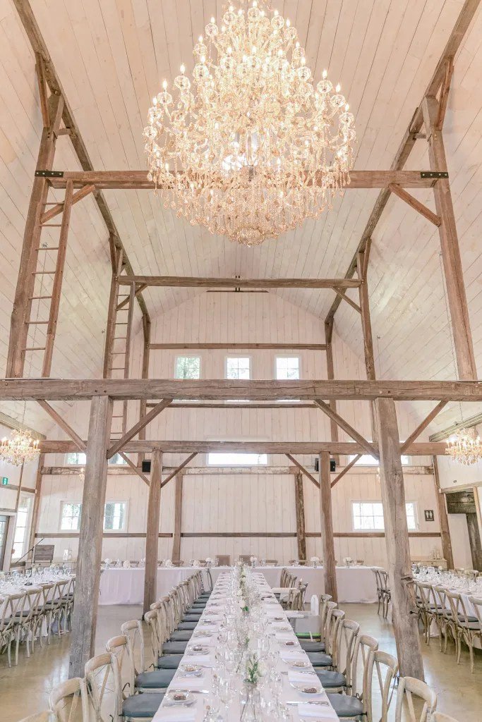 Large Ballroom Chandelier in Modern Barn - Minimalist Decor - Fun shots with Bridesmaids - Rose Gold Sequinned Dresses -  Stonefields Estate-  Bright and Airy - Natural Wedding Posing - Modern Wedding Blush &. Navy Wardrobe inspiration-  Romantic white with greenery, blush and navy theme. Grey Loft Studio is Stonefields Wedding and Engagement Photographer for Real couples, showcasing photos that are modern, bright, and fun.