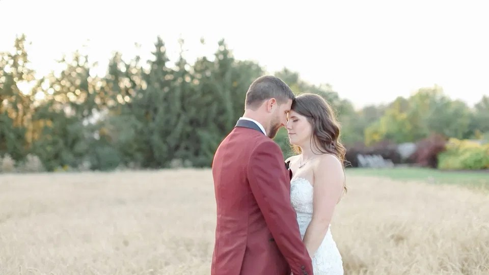 Bride and Groom -Head to Head standing Holding Hands at Sunset - Standing in a Field - Off-White, Silver, Greenery. Eucalyptus Leaves. An inspiration filled with soft neutrals, lush florals, and layers of romantic textures all set at Evermore Weddings and Events, Almonte Ontario.  Grey Loft Studio shot with Canon 5D Mark 4. Ottawa Wedding Photographer & Videographer Team.