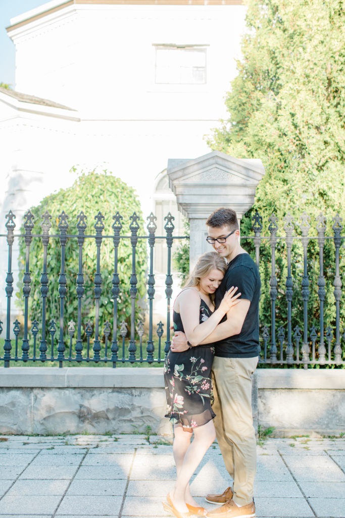 Cuddles while Standing at Rideau Hall - Ideas for what to wear for Engagement Photography, Modern Engagement Session Inspiration Wardrobe Ideas. Unsure of what to wear for your engagement photos, we've got you! Romantic floral dress. Black Polo T-shirt & neutral pants . Boat Shoes and Fancy beaded wedges. Engagement downtown Ottawa. Grey Loft Studio is Ottawa's Wedding and Engagement Photographer Videographer for Real couples, showcasing photos that are modern, bright, and fun.