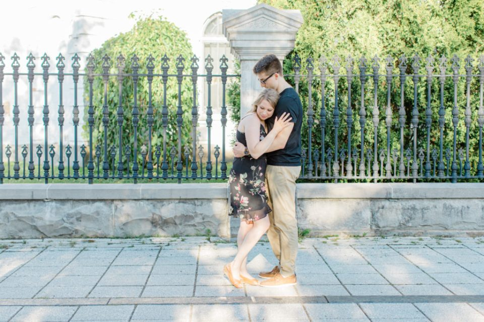 Hugging Photos - Standing at Rideau Hall - Ideas for what to wear for Engagement Photography, Modern Engagement Session Inspiration Wardrobe Ideas. Unsure of what to wear for your engagement photos, we've got you! Romantic floral dress. Black Polo T-shirt & neutral pants . Boat Shoes and Fancy beaded wedges. Engagement downtown Ottawa. Grey Loft Studio is Ottawa's Wedding and Engagement Photographer Videographer for Real couples, showcasing photos that are modern, bright, and fun.