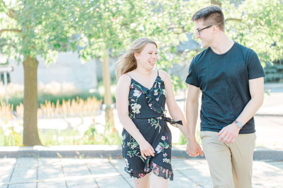 Laughing while posing at Rideau Hall - Ideas for what to wear for Engagement Photography, Modern Engagement Session Inspiration Wardrobe Ideas. Unsure of what to wear for your engagement photos, we've got you! Romantic floral dress. Black Polo T-shirt & neutral pants . Boat Shoes and Fancy beaded wedges. Engagement downtown Ottawa. Grey Loft Studio is Ottawa's Wedding and Engagement Photographer Videographer for Real couples, showcasing photos that are modern, bright, and fun.