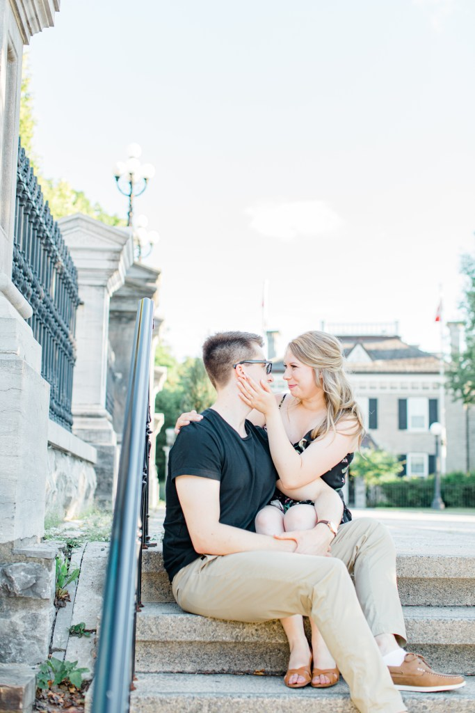 Cute couple Posing while sitting on steps at Rideau Hall - Ideas for what to wear for Engagement Photography, Modern Engagement Session Inspiration Wardrobe Ideas. Unsure of what to wear for your engagement photos, we've got you! Romantic floral dress. Black Polo T-shirt & neutral pants . Boat Shoes and Fancy beaded wedges. Engagement downtown Ottawa. Grey Loft Studio is Ottawa's Wedding and Engagement Photographer Videographer for Real couples, showcasing photos that are modern, bright, and fun.