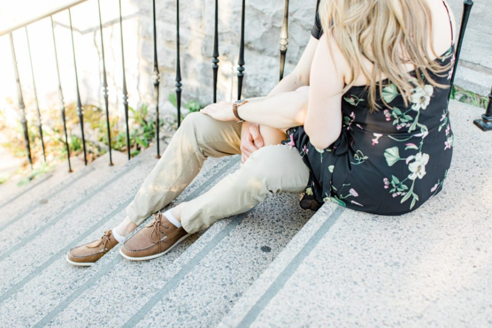 Engagement Photo Poses- Cute couple Posing while sitting on steps at Rideau Hall - Ideas for what to wear for Engagement Photography, Modern Engagement Session Inspiration Wardrobe Ideas. Unsure of what to wear for your engagement photos, we've got you! Romantic floral dress. Black Polo T-shirt & neutral pants . Boat Shoes and Fancy beaded wedges. Engagement downtown Ottawa. Grey Loft Studio is Ottawa's Wedding and Engagement Photographer Videographer for Real couples, showcasing photos that are modern, bright, and fun.