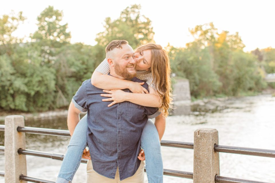 Kissing during piggy back pose - Watson's Mill Engagement Session Manotick - Bright & Airy photography - Grey Loft Studio - Ottawa Wedding Photographer - Ottawa Wedding Videographer - Engagement Session Locations in Ottawa - Summer Engagement session - Light blue and Cream with casual jeans and strap sandals. Ottawa Photo Studio.