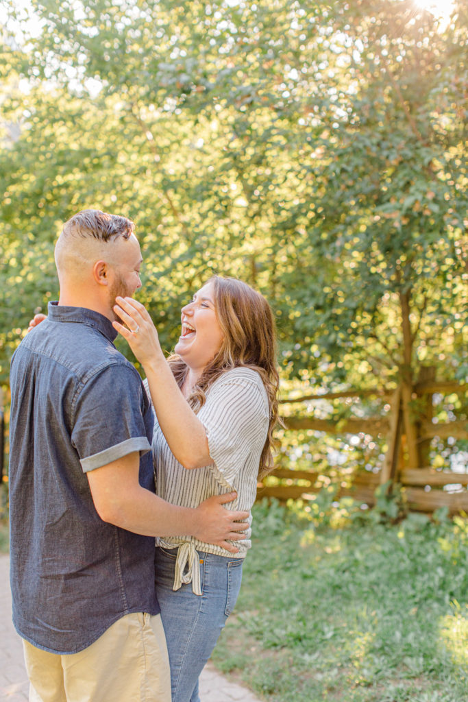 Couple holding each other close and walking looking back -engagement session - Watson's Mill Engagement Session Manotick - Bright & Airy photography - Grey Loft Studio - Ottawa Wedding Photographer - Ottawa Wedding Videographer - Engagement Session Locations in Ottawa - Summer Engagement session - Light blue and Cream with casual jeans and strap sandals. Ottawa Photo Studio.