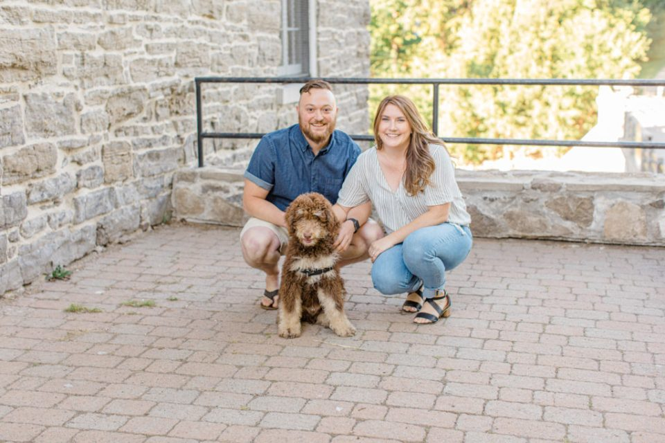 Chocolate Golden Doodle Puppy - grey loft studio -engagement session - Watson's Mill Engagement Session Manotick - Bright & Airy photography - Grey Loft Studio - Ottawa Wedding Photographer - Ottawa Wedding Videographer - Engagement Session Locations in Ottawa - Summer Engagement session - Light blue and Cream with casual jeans and strap sandals. Ottawa Photo Studio.