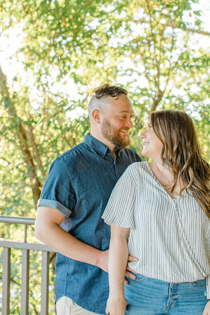 Look at the camera while holding hands- Couple holding each other close -engagement session - Watson's Mill Engagement Session Manotick - Bright & Airy photography - Grey Loft Studio - Ottawa Wedding Photographer - Ottawa Wedding Videographer - Engagement Session Locations in Ottawa - Summer Engagement session - Light blue and Cream with casual jeans and strap sandals. Ottawa Photo Studio.