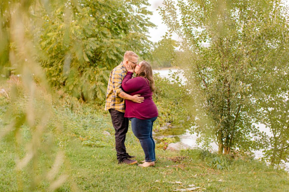 Kissing under Willow Tree by the Water- Engagement Session - Ottawa Wedding Photographer - Grey Loft Studio - Wedding in Ottawa - Yellow & Plaid with Burgundy Knit Sweater and Jeans