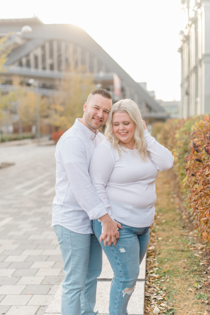 Husband & Wife posing in Downtown Ottawa at Lansdowne Park - Sunny Fall Day shot at Sunset - wearing white shirts and blue jeans Grey Loft Studio - Ottawa Wedding Photographer - Wedding Photo Studio - Matching couple - Poses ideas - Photoshoot ideas - Photoshoot location