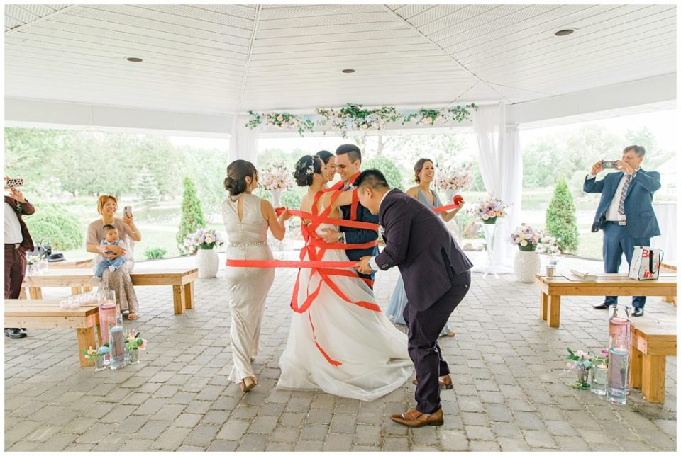 Traditional wrapping of streamers around bride & groom during first dance - Italian & Chinese Family - Wedding - Lisa & Pat - Grey Loft Studio - Wedding Photo & Video Team - Light and Airy - Ottawa Wedding Photographer & Videographer Orchard View Weddings