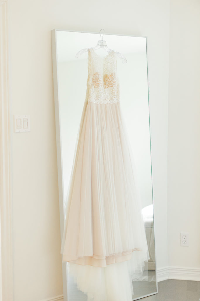 Dress hanging on a Mirror - Rose coloured tule with a lace Bodice. This lovely gown from White Satin Bridal Boutique.